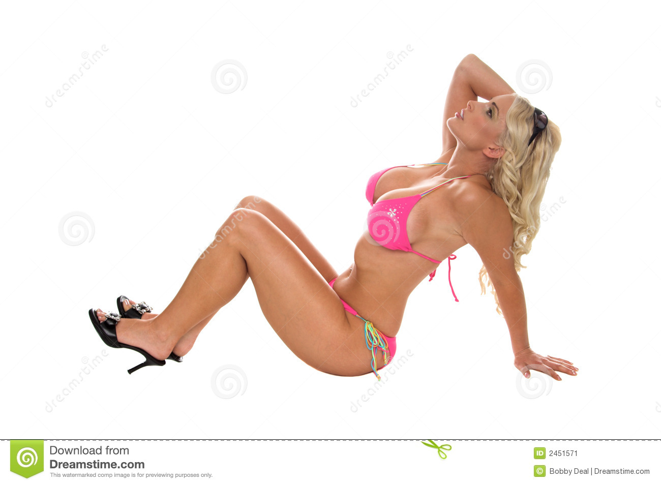 Sexy blond bikini pinup model in a fuchsia bikini. sitting on the ...