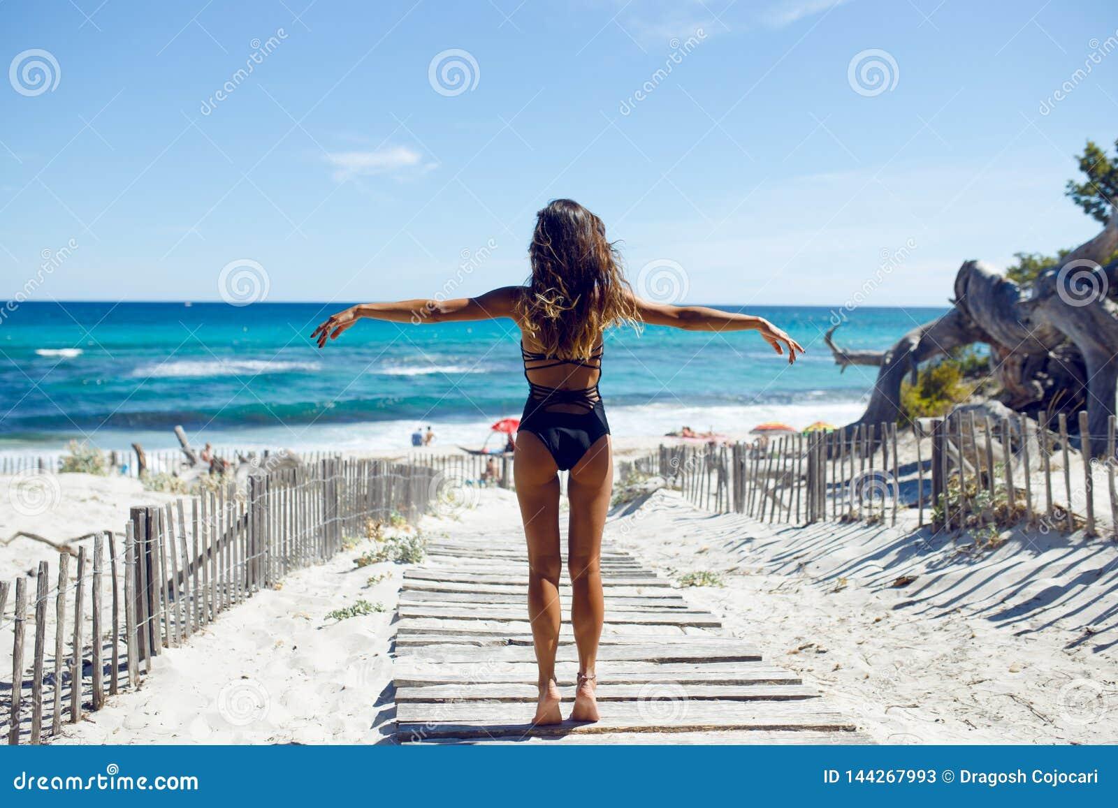 Bikini que lleva de la mujer atractiva en la playa La hembra joven en el traje de baño que se colocaba en la costa con sus manos