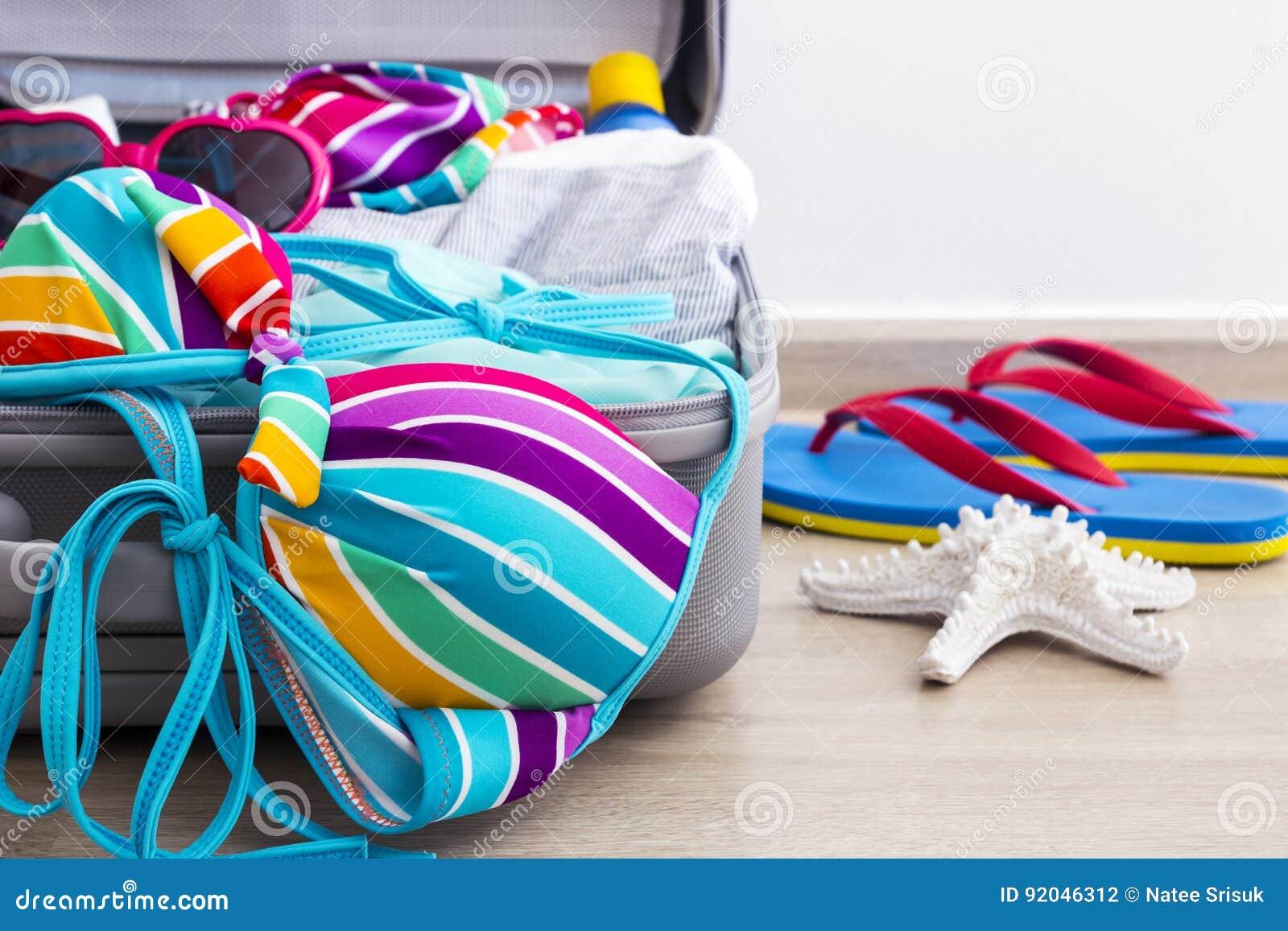 Bikini y ropa coloridos en equipaje en el piso laminado