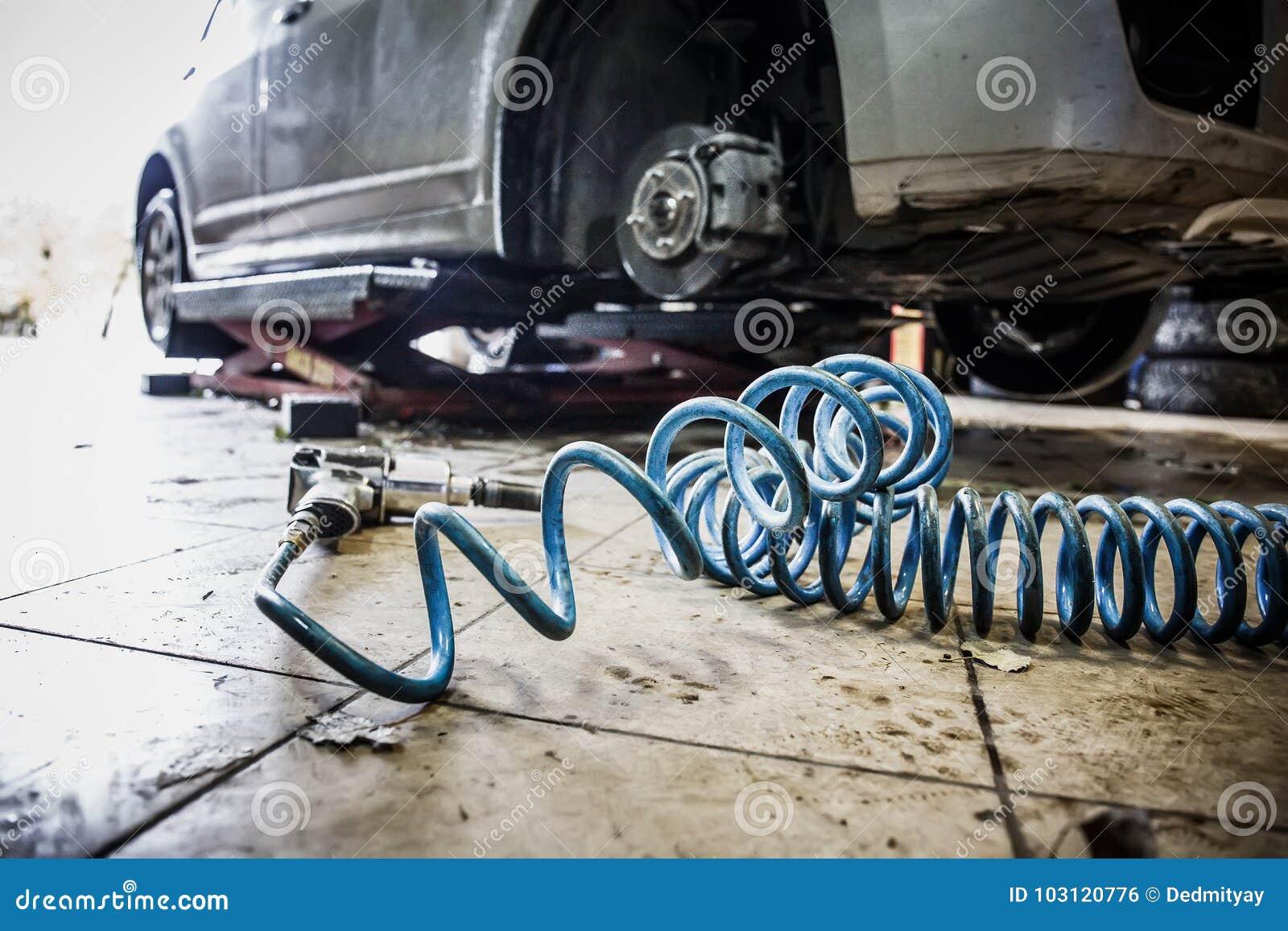 Bil i garage i för reparationsservice för auto mekaniker seminarium med den speciala maskinen som reparerar utrustning - pneumati