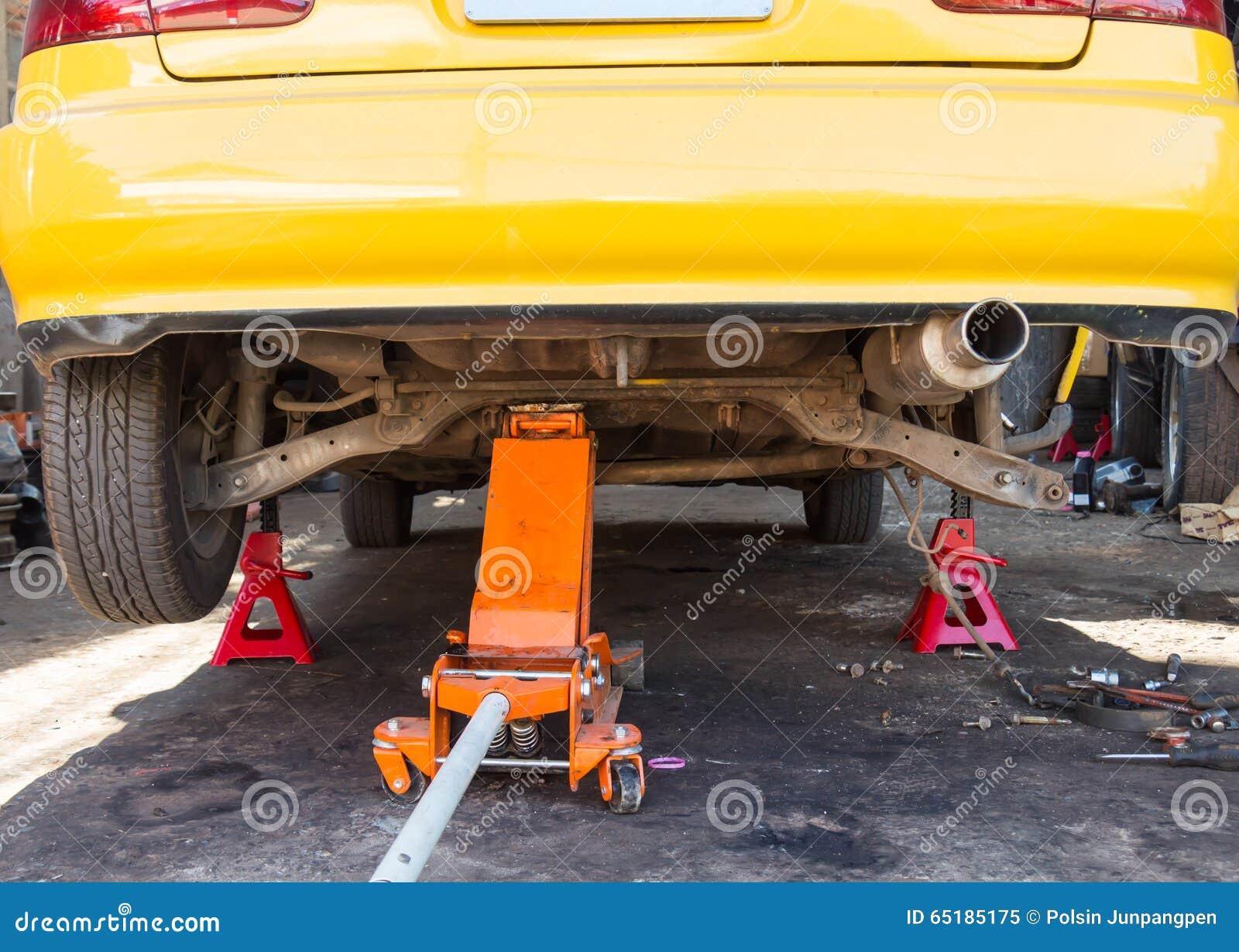 Bil med en stålar som lyfter det bakre hjulet för bromsreparation