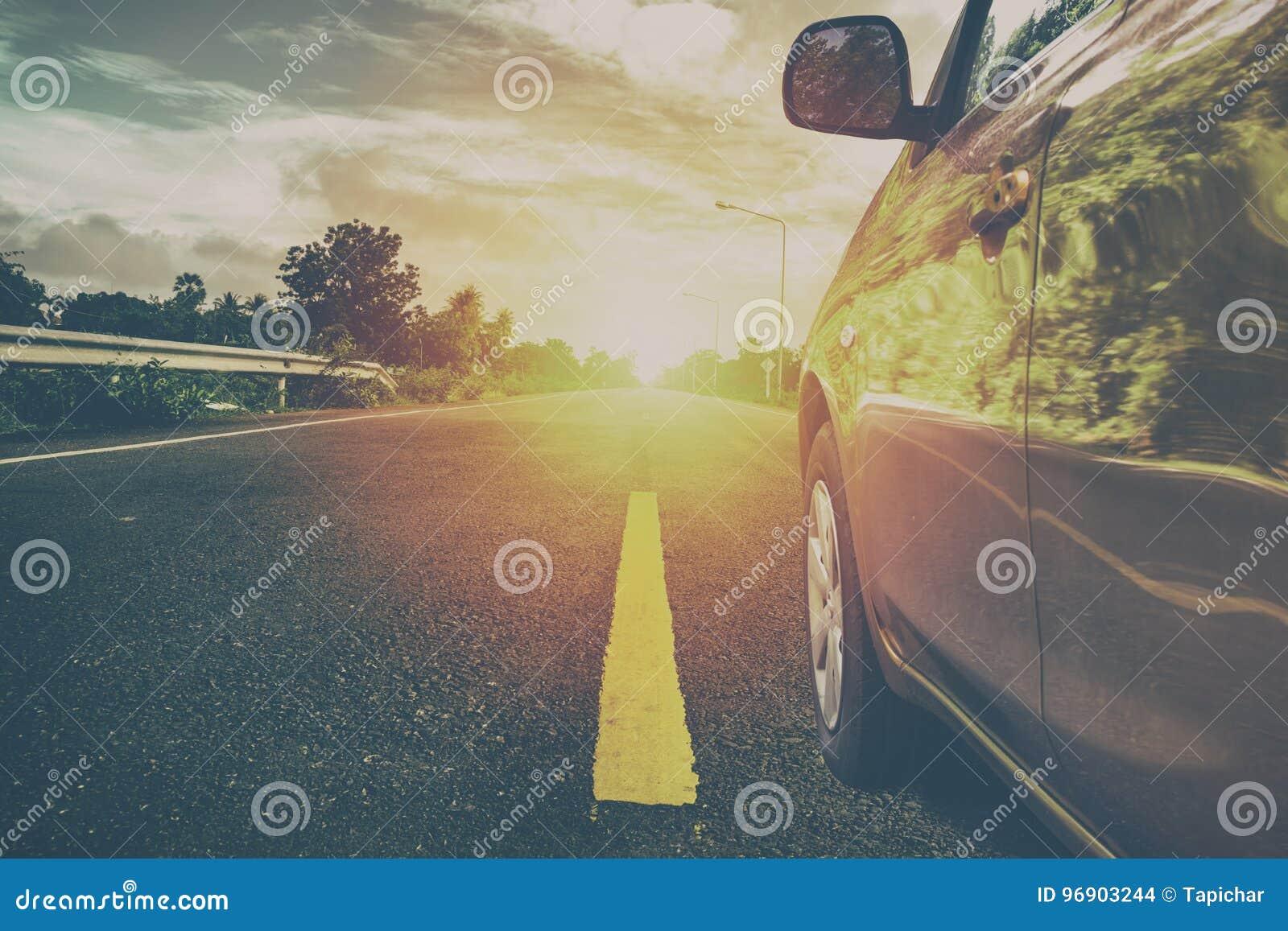 Bil på vägen på soluppgång