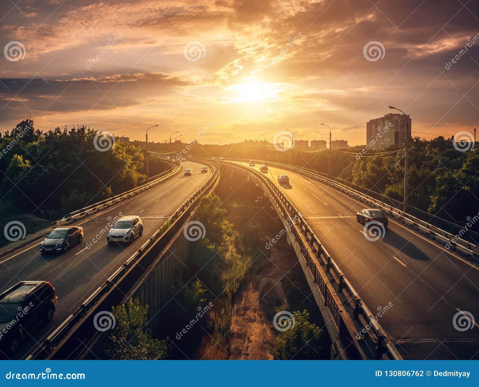 Bilar för stads- trafik kör på solnedgången på huvudvägen i cityscapesommarplatsen, stadstrans.begrepp