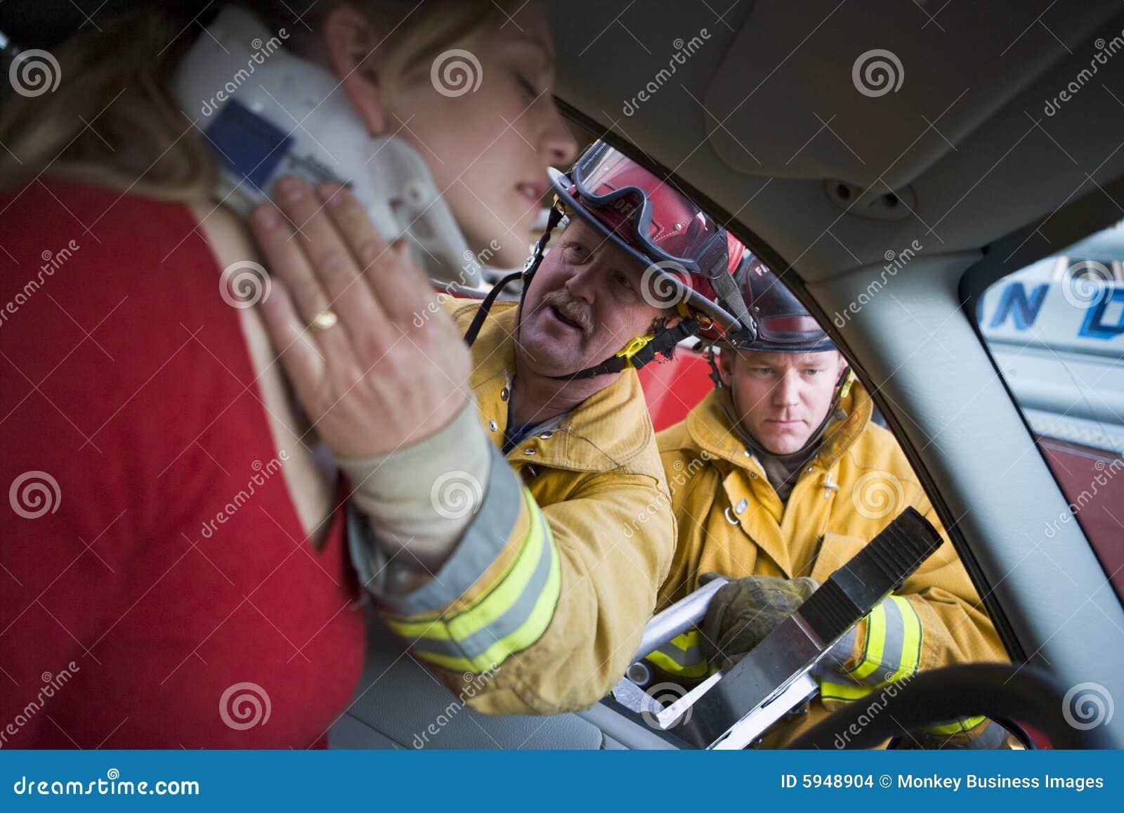 Bilbrandmän som hjälper den sårada kvinnan