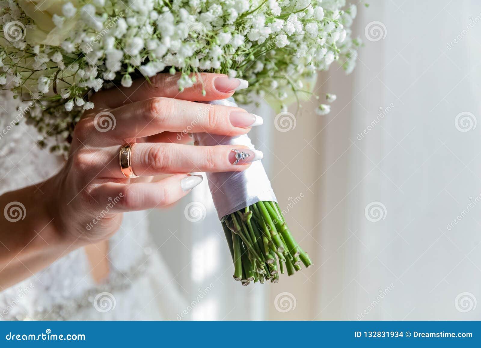 Bild av att gifta sig buketten i bruds händer