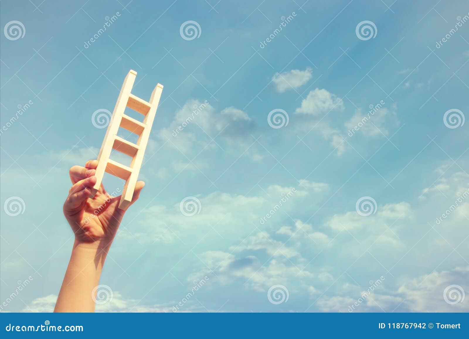 Bild av barnhanden som rymmer en stege mot himlen Utbildning och framgångbegrepp