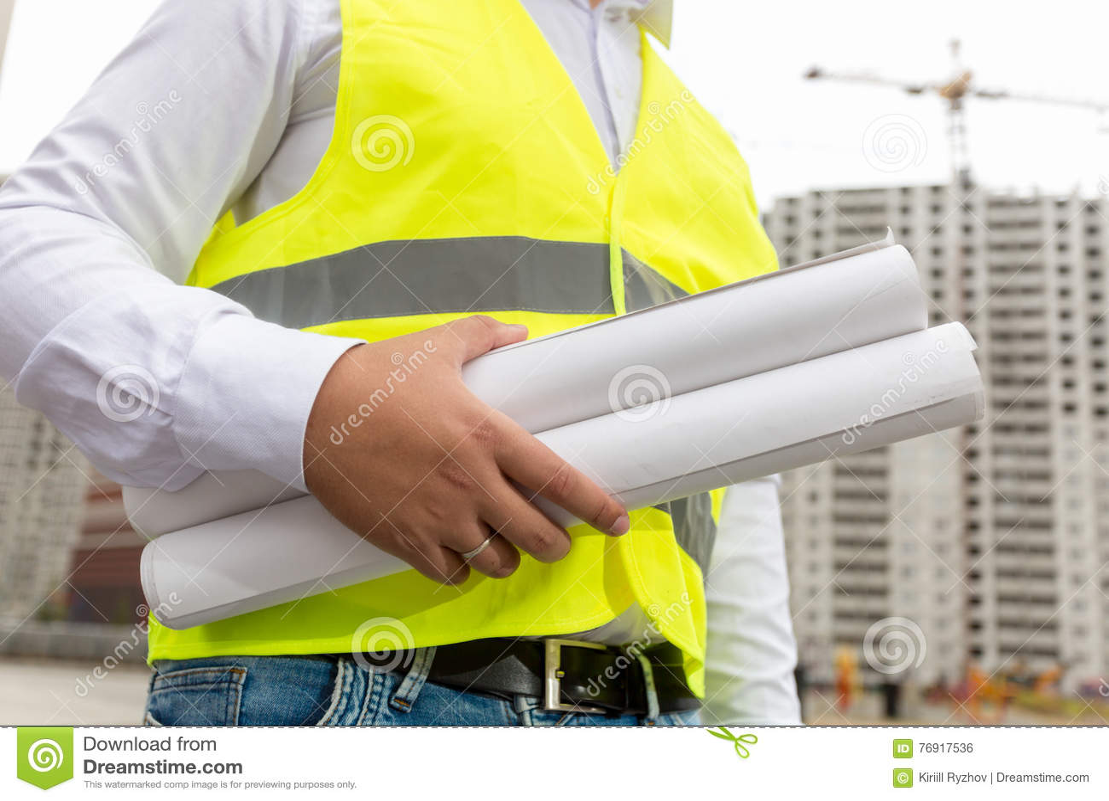 Bild av den manliga konstruktionsteknikern med rullande ritningar på bu