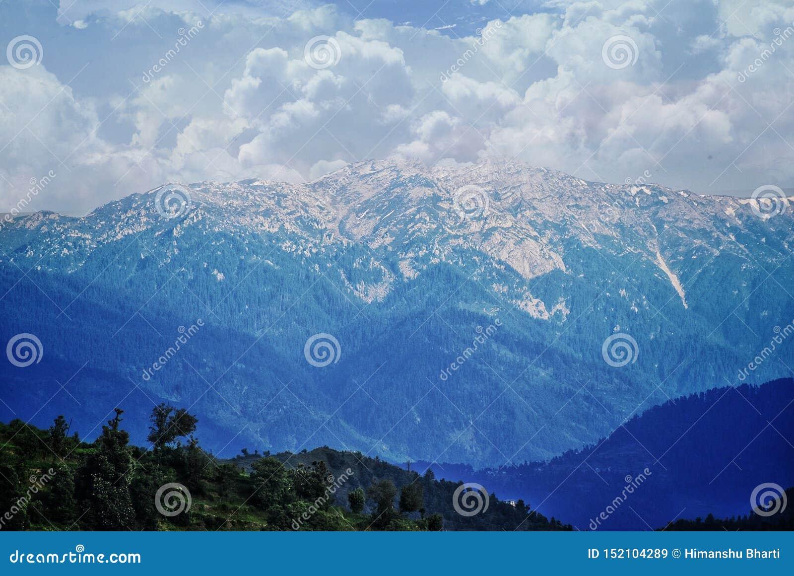Bild av ett himalayan berg med snö och moln på den