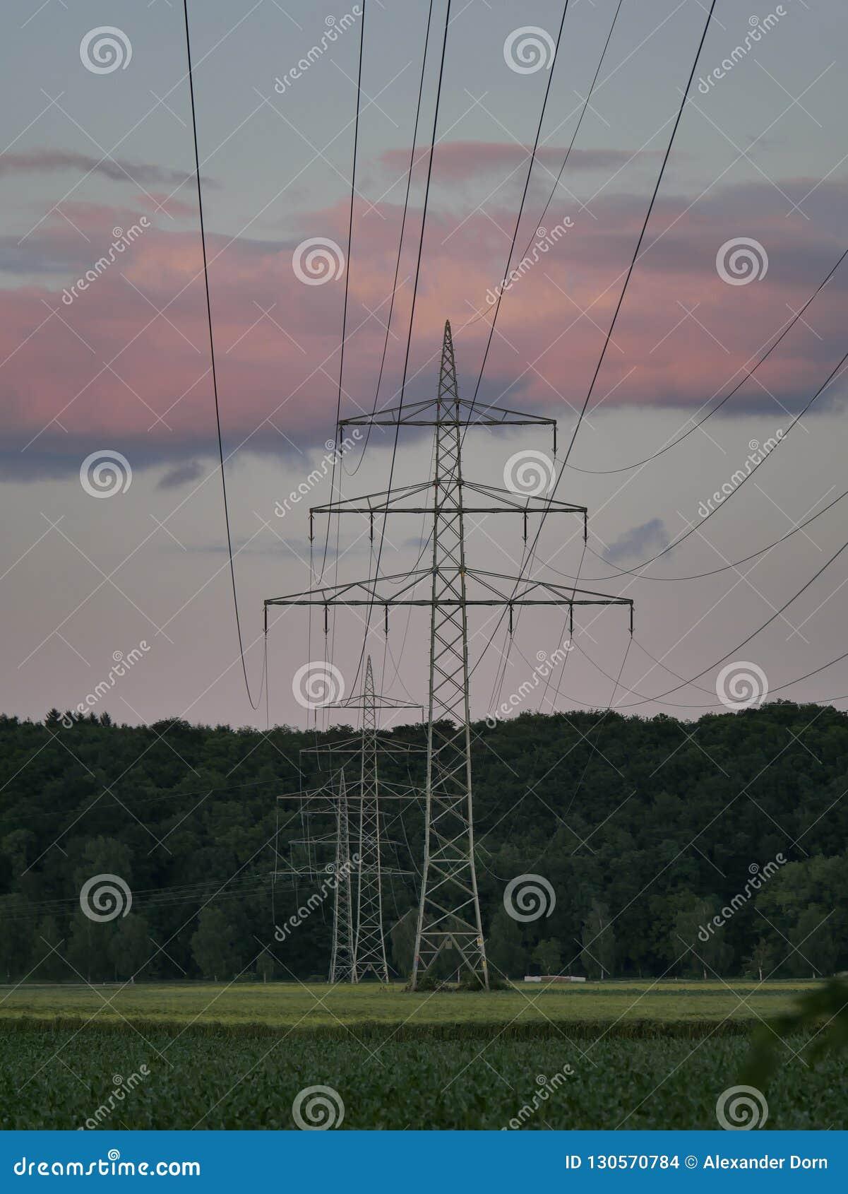 Bild av kraftledningen under solnedgång med kraftverket