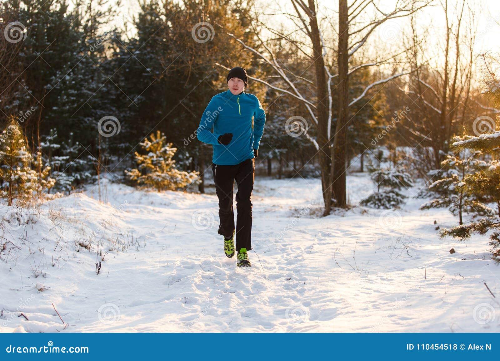Bild av ung idrottsman nenspring till och med vinterskog