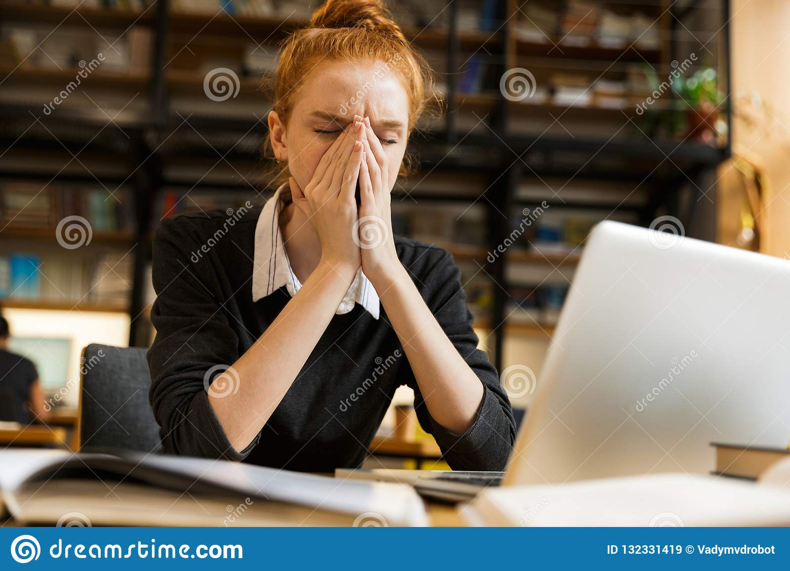 Bild der ernsten studierenden Rothaarigefrau, beim Sitzen an Schreibtisch I