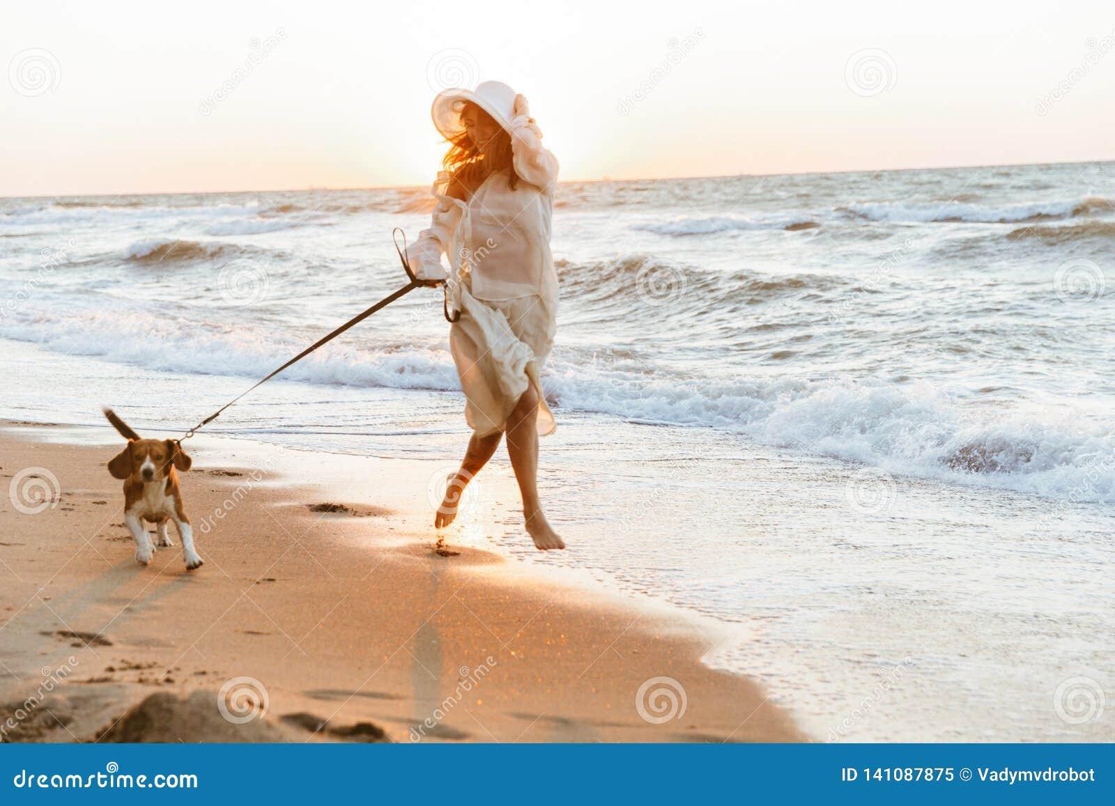 Bild der europäischen Frau 20s im Sommerstrohhut, laufend durch Küste mit ihrem Hund