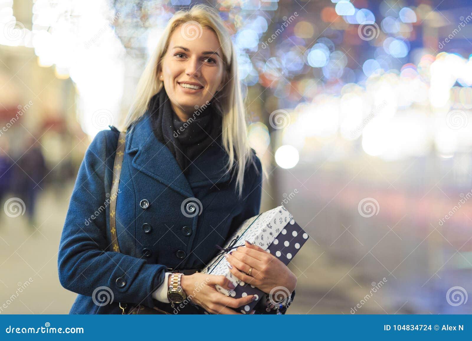 Bild der Frau im Mantel mit Geschenk im Kasten