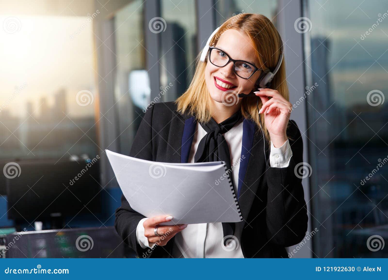 Bild der lächelnden Frau mit Gläsern und Kopfhörern mit Papier in den Händen nahe Glaswand