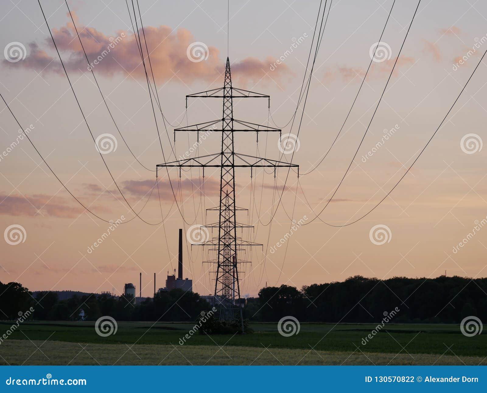 Bild der Stromleitung während des Sonnenuntergangs mit Kraftwerk