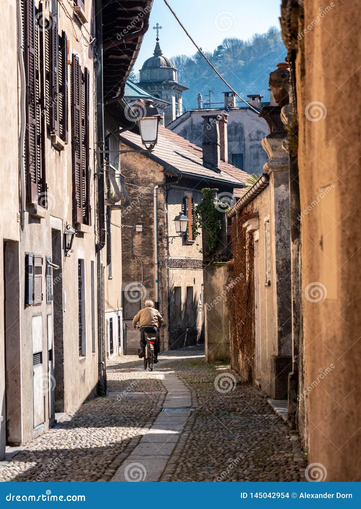 Bild des alten Mannes von hinten das Radfahren durch schmale Straße in einer italienischen alten Stadt