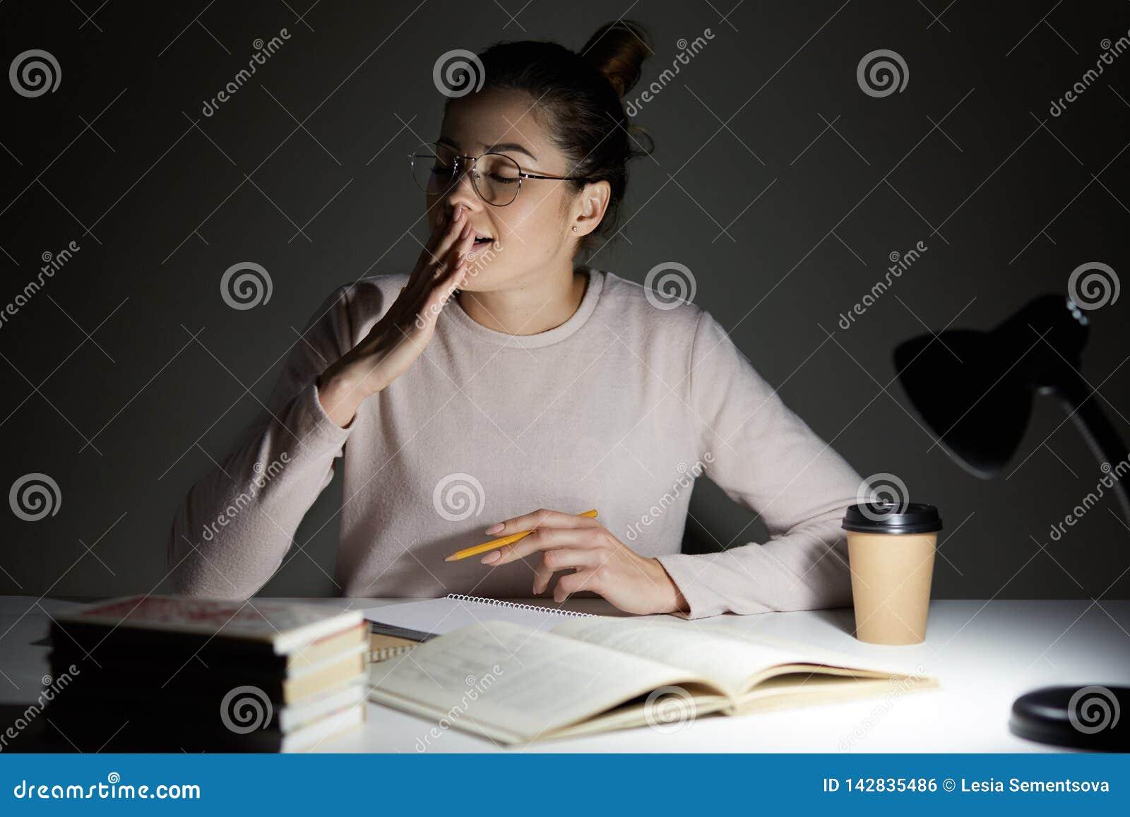 Bild des attraktiven seepy Studentengegähnes mit geschlossenen Augen, sitzt am Desktop beim Vorbereiten für Klassen, Arbeitsübers