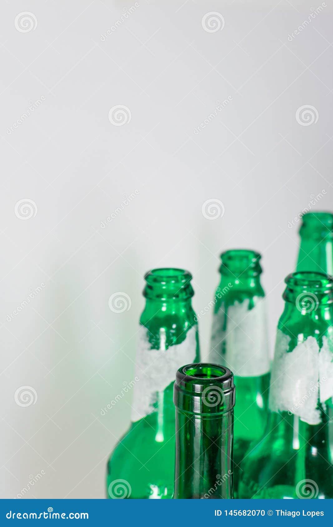 Bild des Engpasses der leeren Bier- und Weingr?nglasflaschen auf einem wei?en Hintergrund Wiederverwendung, acoholism, bereiten a