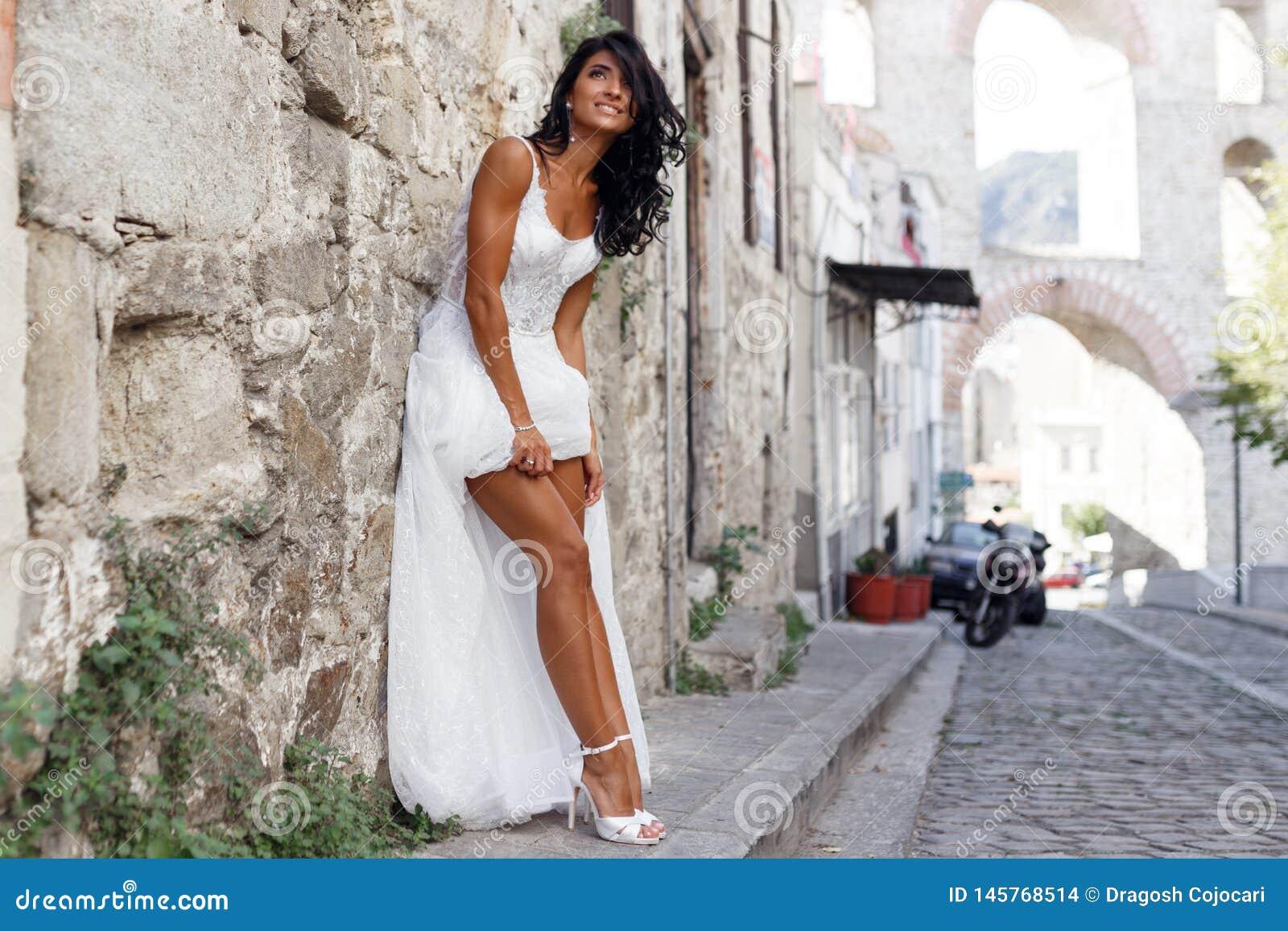 Bild einer herrlichen brunette Braut wirft sinnliches nahe alter Stadt in Griechenland, Sommerzeit auf Hochzeit in Griechenland