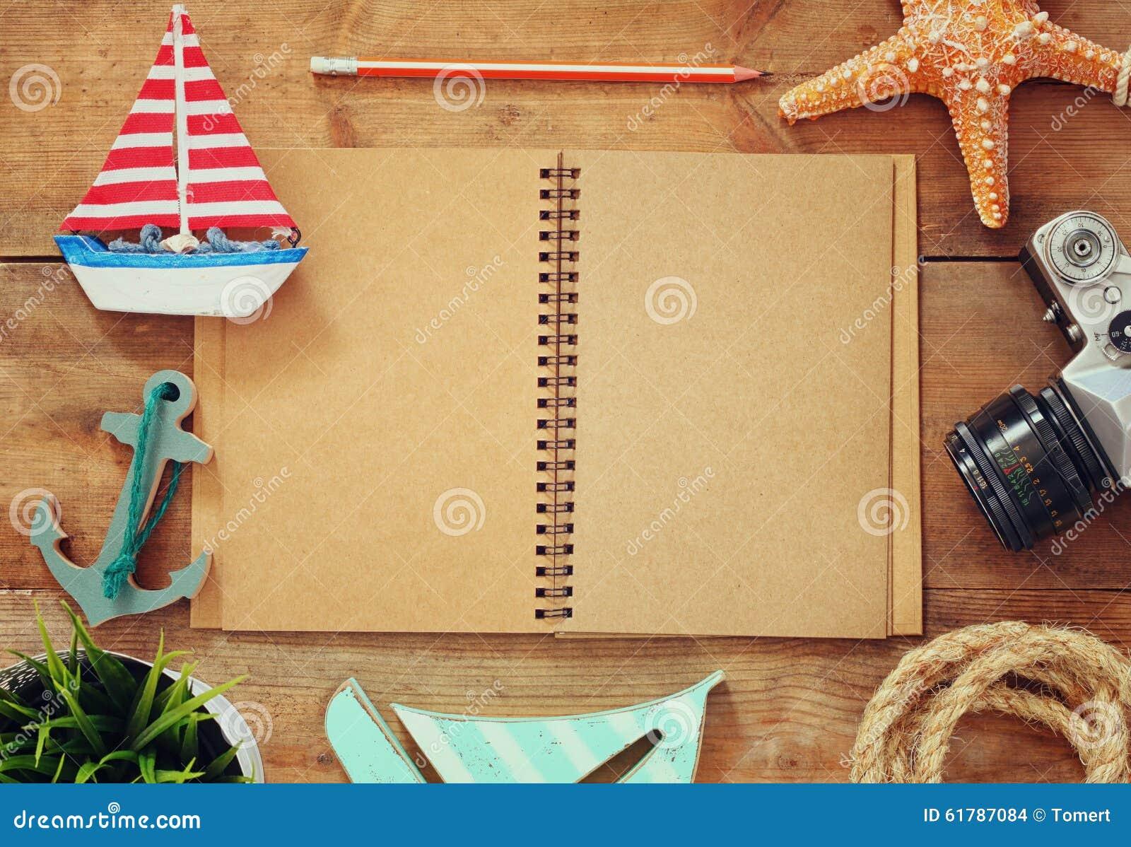 Bild för bästa sikt av den öppna tomma anteckningsboken, träsegelbåten, nautiskt moget och kameran Lopp- och affärsföretagbegrepp