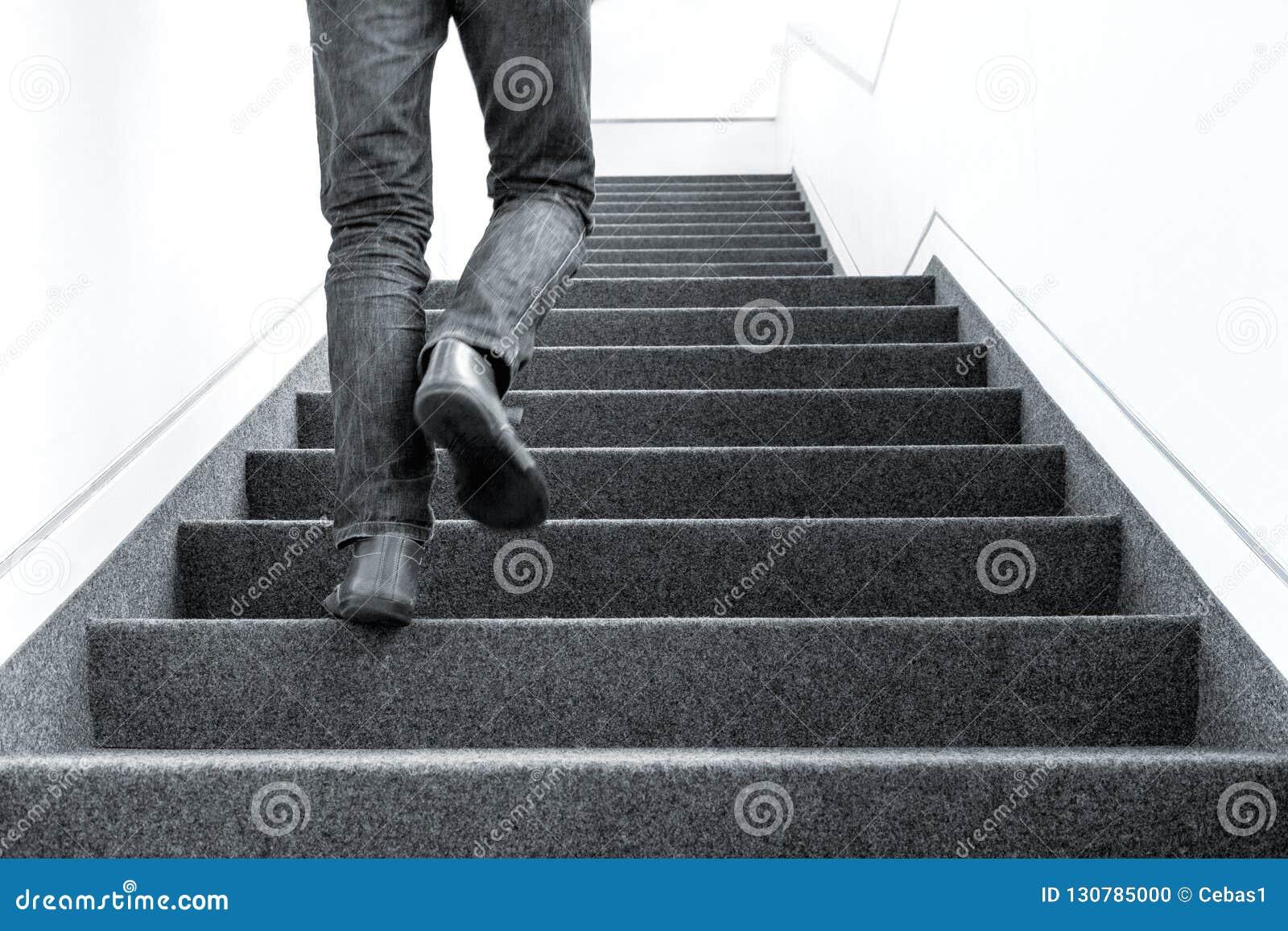 Bild för låg vinkel av mannen som uppför trappan går på inomhus