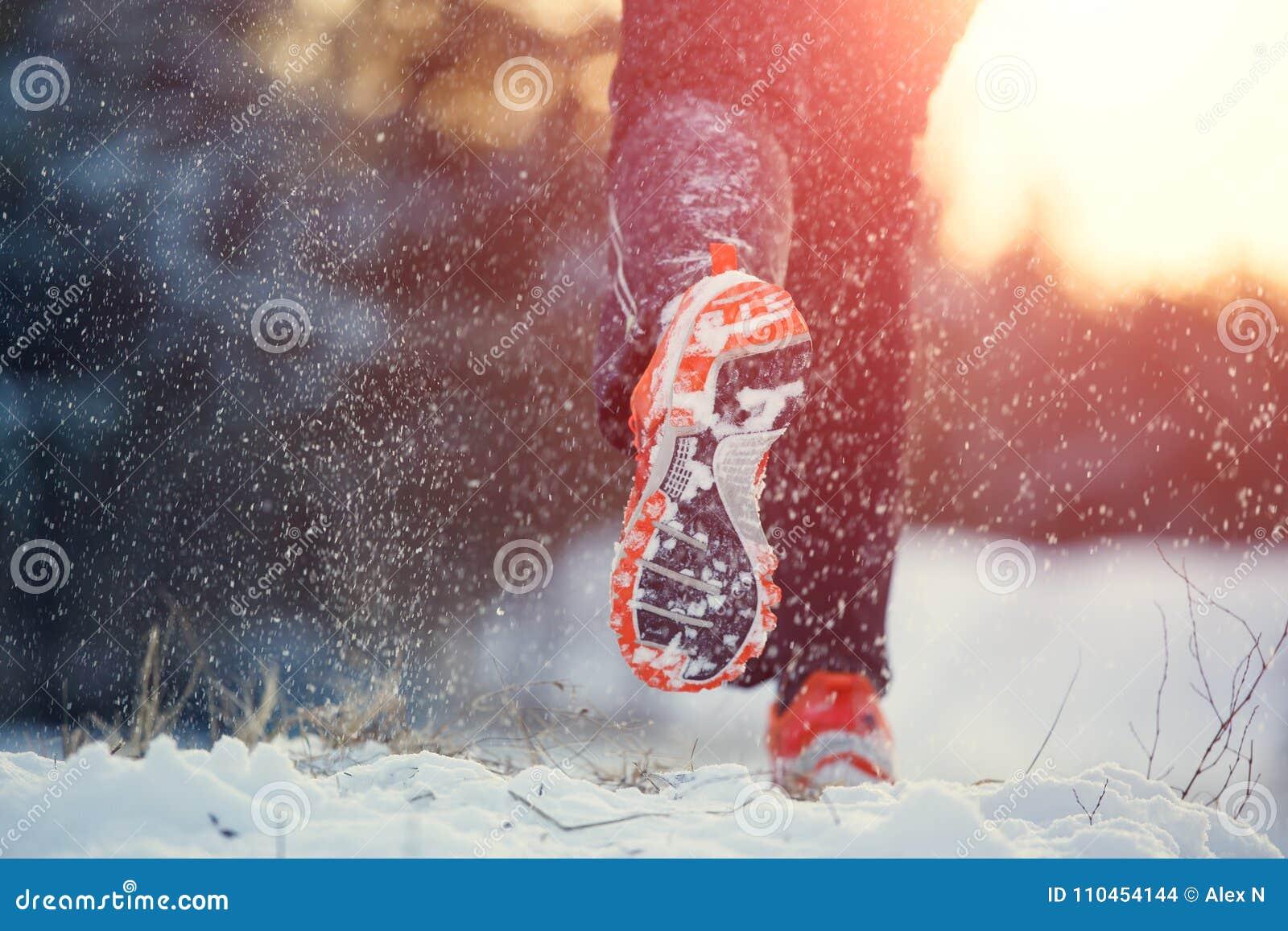 Bild från baksida av den rinnande mannen i gymnastikskor i sportkläder på snö
