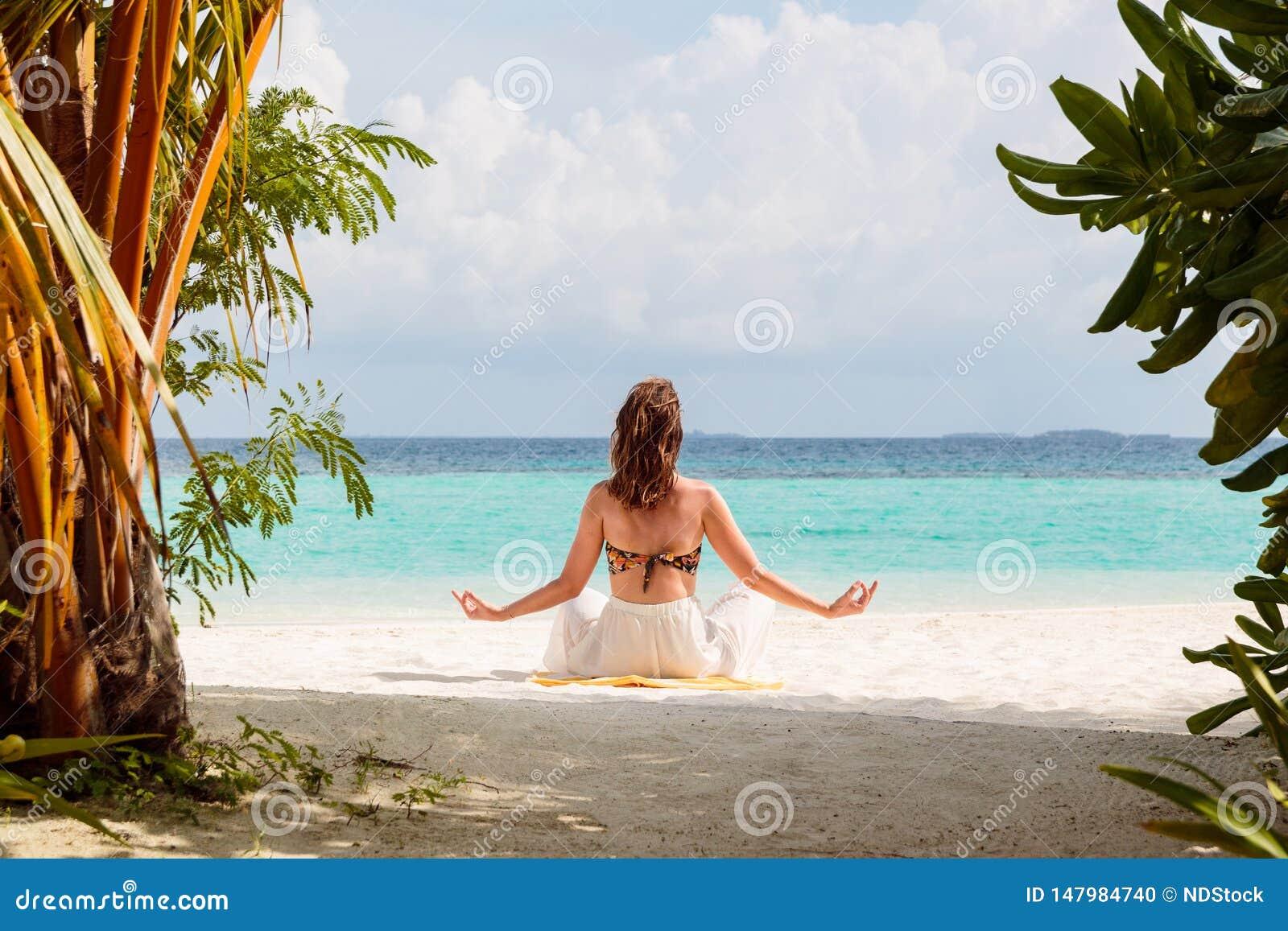 Bild från baksida av en ung kvinna som mediterar på en strand i Maldiverna