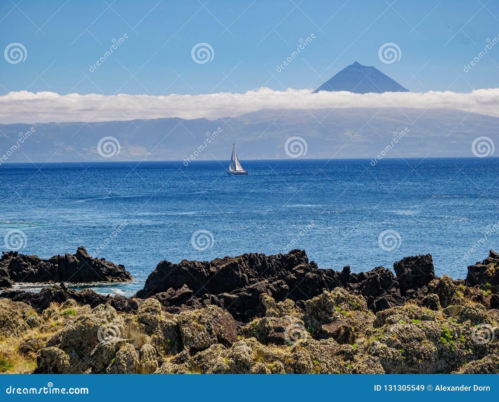 Bild från en klippa med en segelbåt i det atlantiskt och ön av Pico med berget Pico i bakgrunden