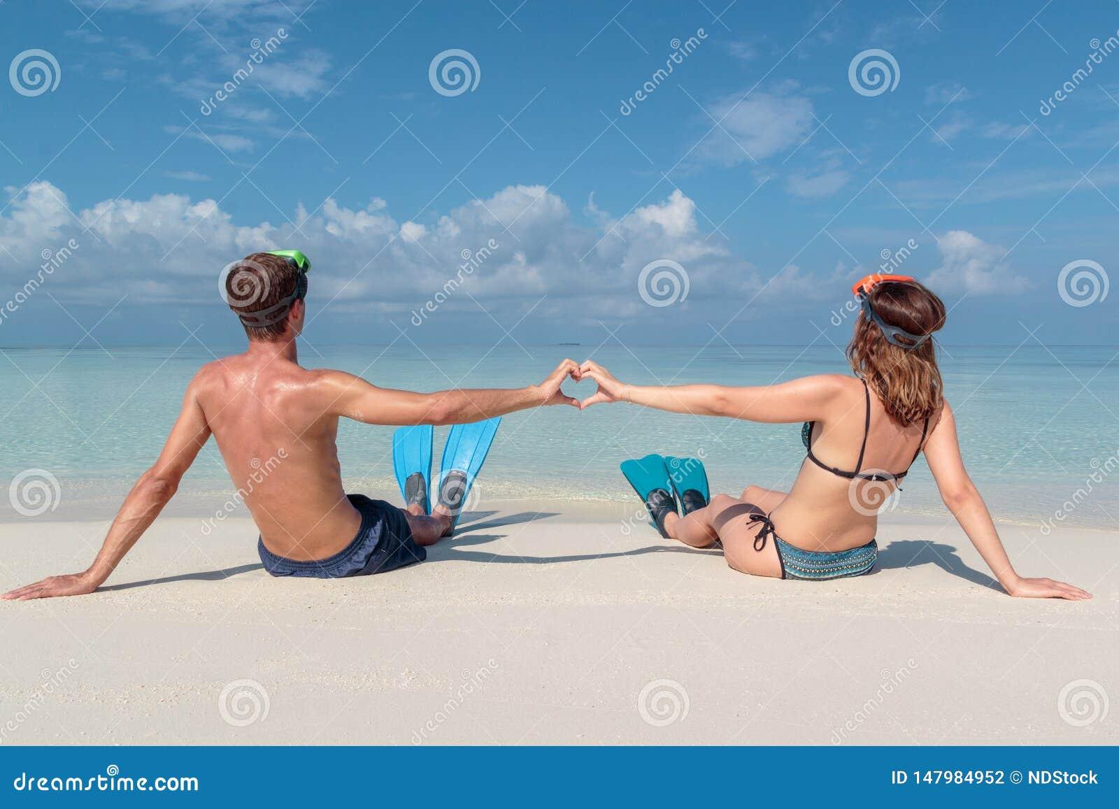 Bild fr?n baksida av ett ungt par med flipper och maskeringen som placeras p? en vit strand i Maldiverna Kristallklart bl?tt vatt