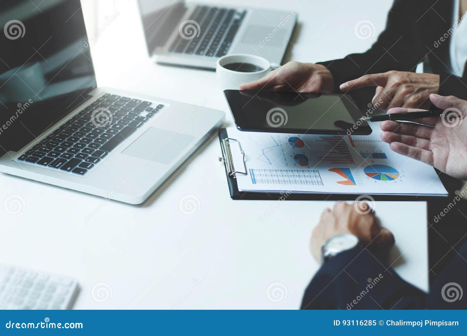 Bild von zwei jungen Unternehmensleitern, die Berührungsfläche bei der Sitzung verwenden
