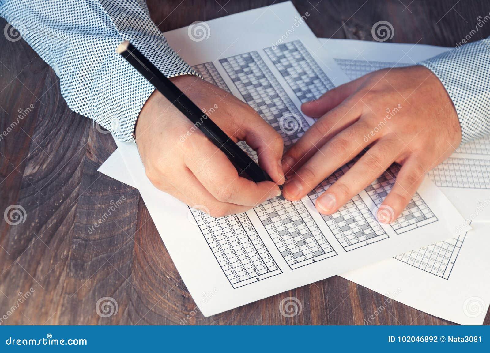 Bilda för examen för mannen på tabellen Provning för utbildning och att hyra Högerhänt och vänsterhänt Selektivt fokusera ton
