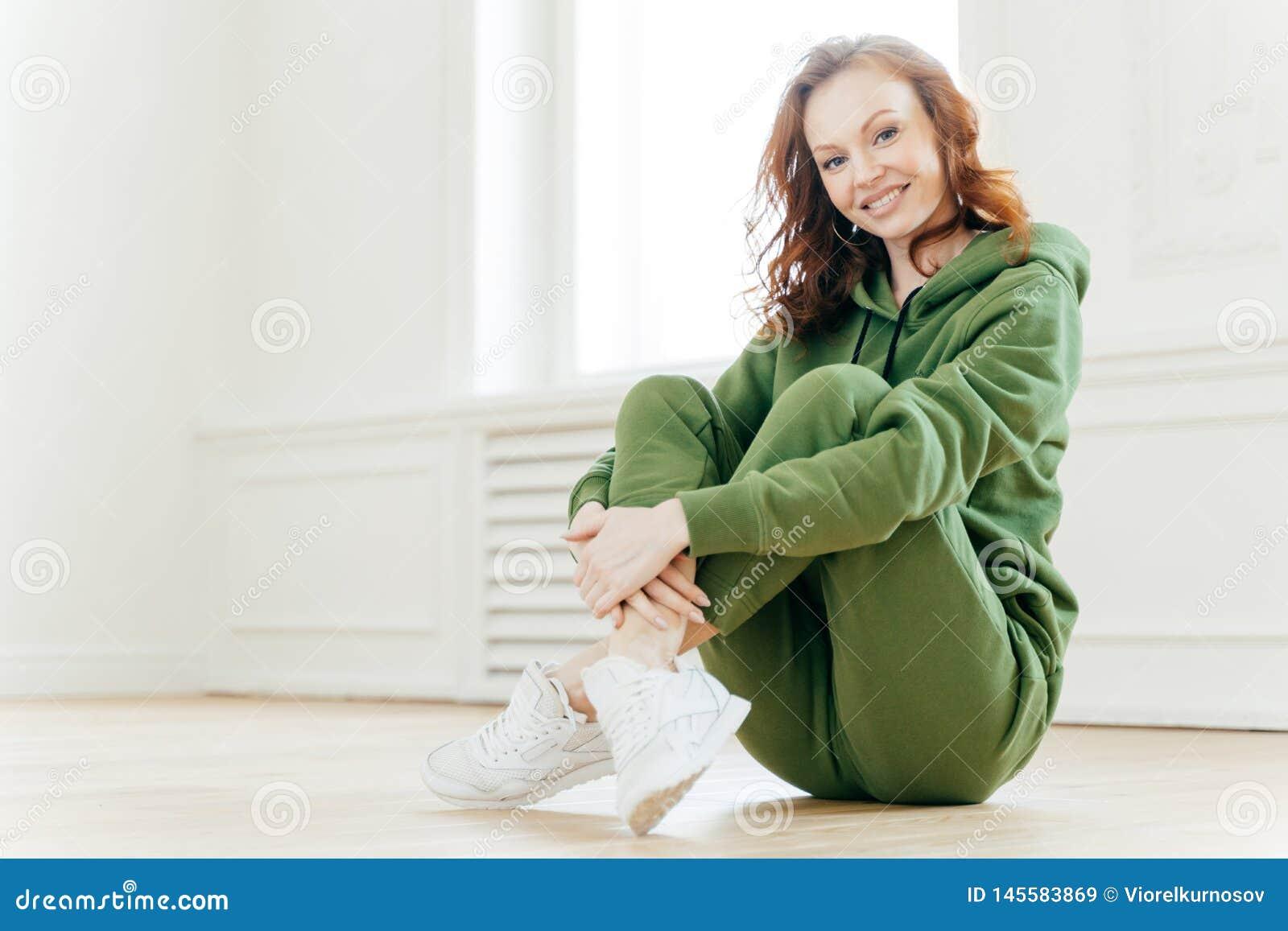 Bilden av den tillfredsställda förnyade unga kvinnan med rävaktigt hår, håller ben korsade, bär träningsoverallen och sportshoes