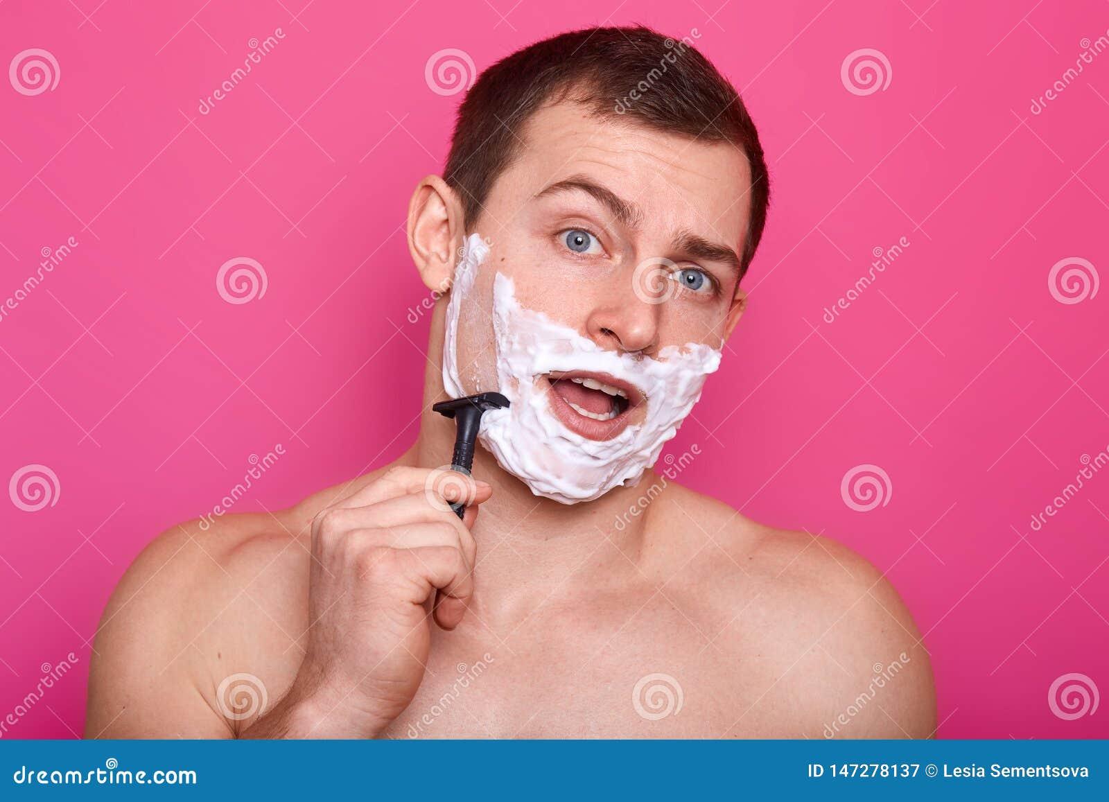 Bilden av den unga mannen som poserar med den öppna munnen och att raka i badrum och sjunga, håller rakkniven i handen, ställning