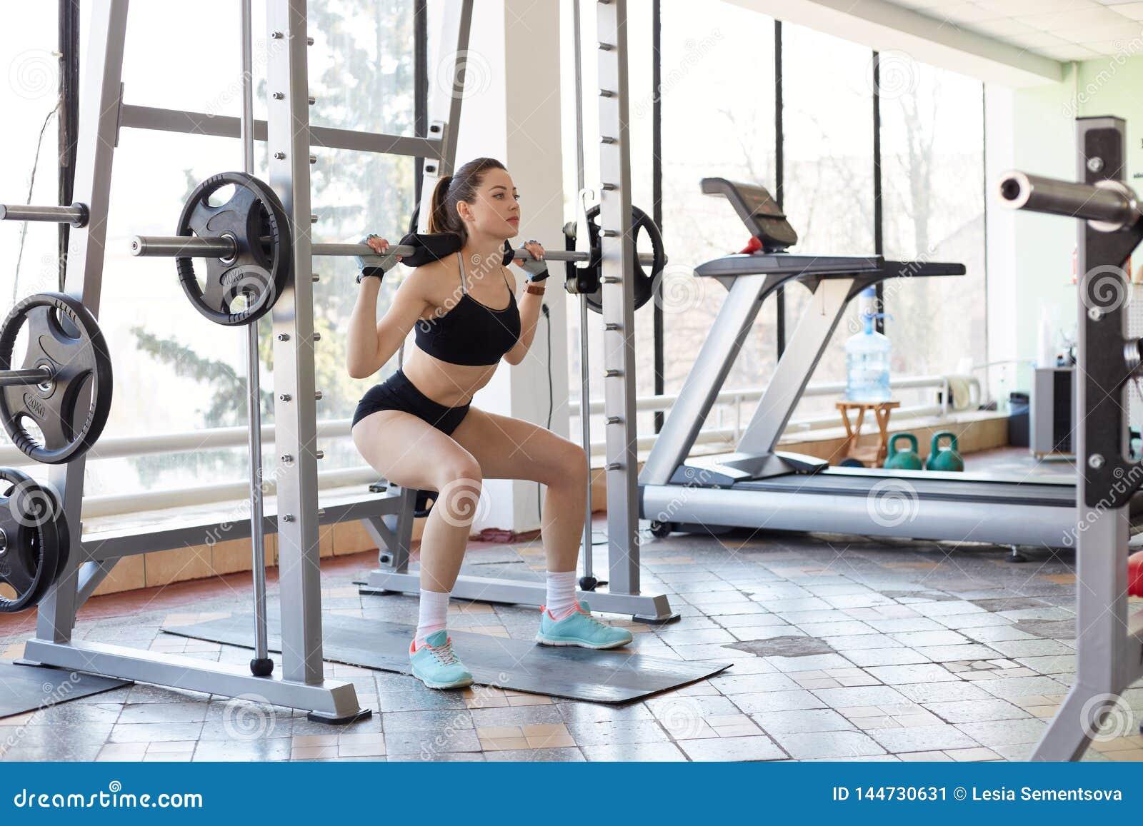 Bilden av den yrkesmässiga idrottskvinnan som gör övning i idrottshallen, squats med skivstången, lyfter vikter, framkallar s