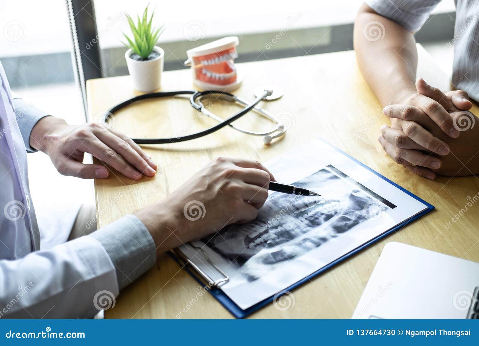 Bilden av doktorn eller tandläkaren som framlägger med tandröntgenstrålefilmen, rekommenderar tålmodig i behandlingen av tand- oc