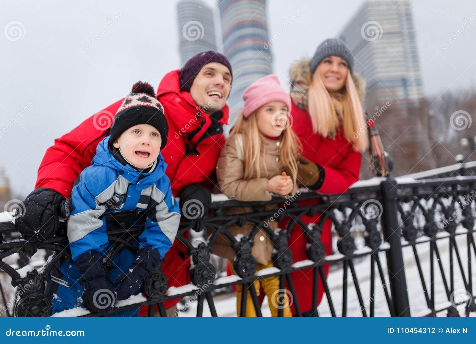Bilden av föräldrar med barn på vinter går