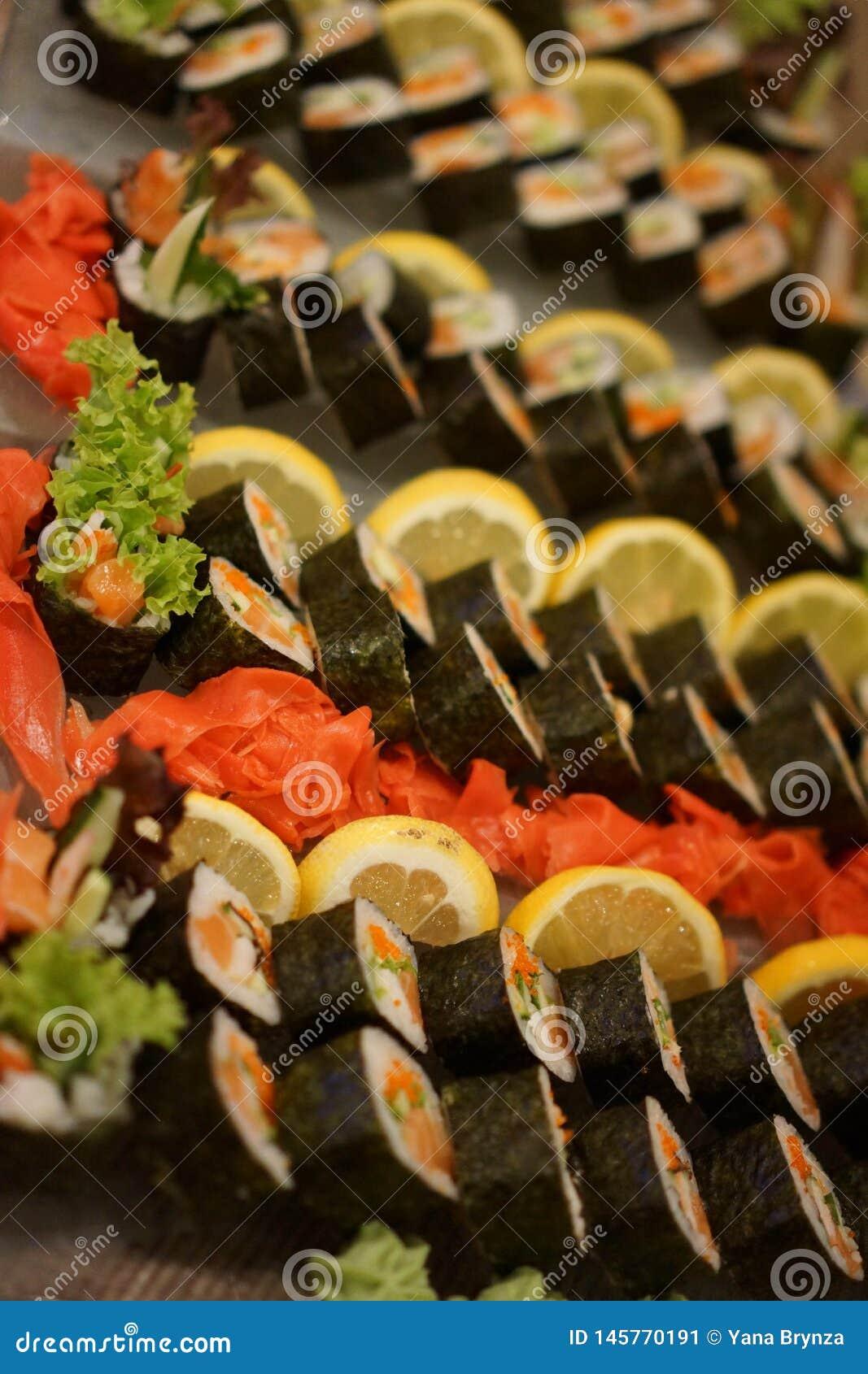 Bilder av ny sushidisk med en stor variation som dekoreras med citronen och den färgrika ingefäran med grönsallatsidor Selektivt
