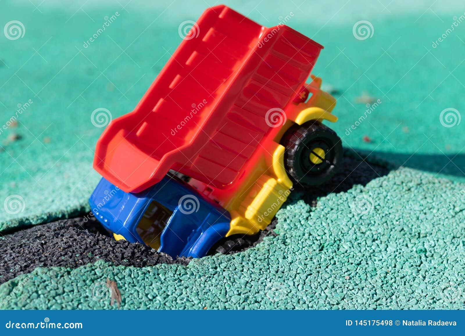 Bilen avverkar in i gropen Hade den plast- lastbilen för leksaken med en röd kropp en olycka Hål på Asphalt Coating Vägen be
