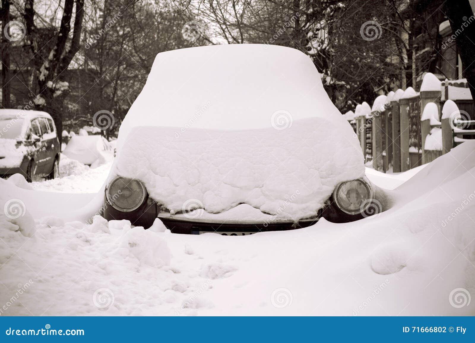 Bilen klibbade i snö på en gata med endast billyktauppvisning