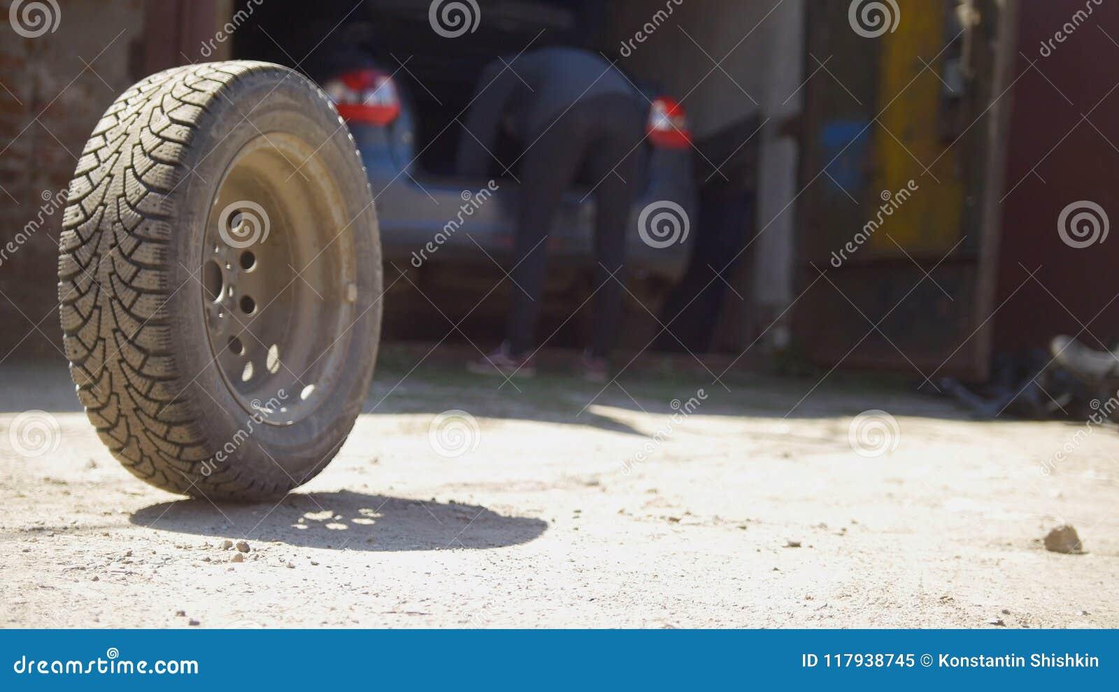 Bilhjul som framme rullar på jordningen av bilgaraget
