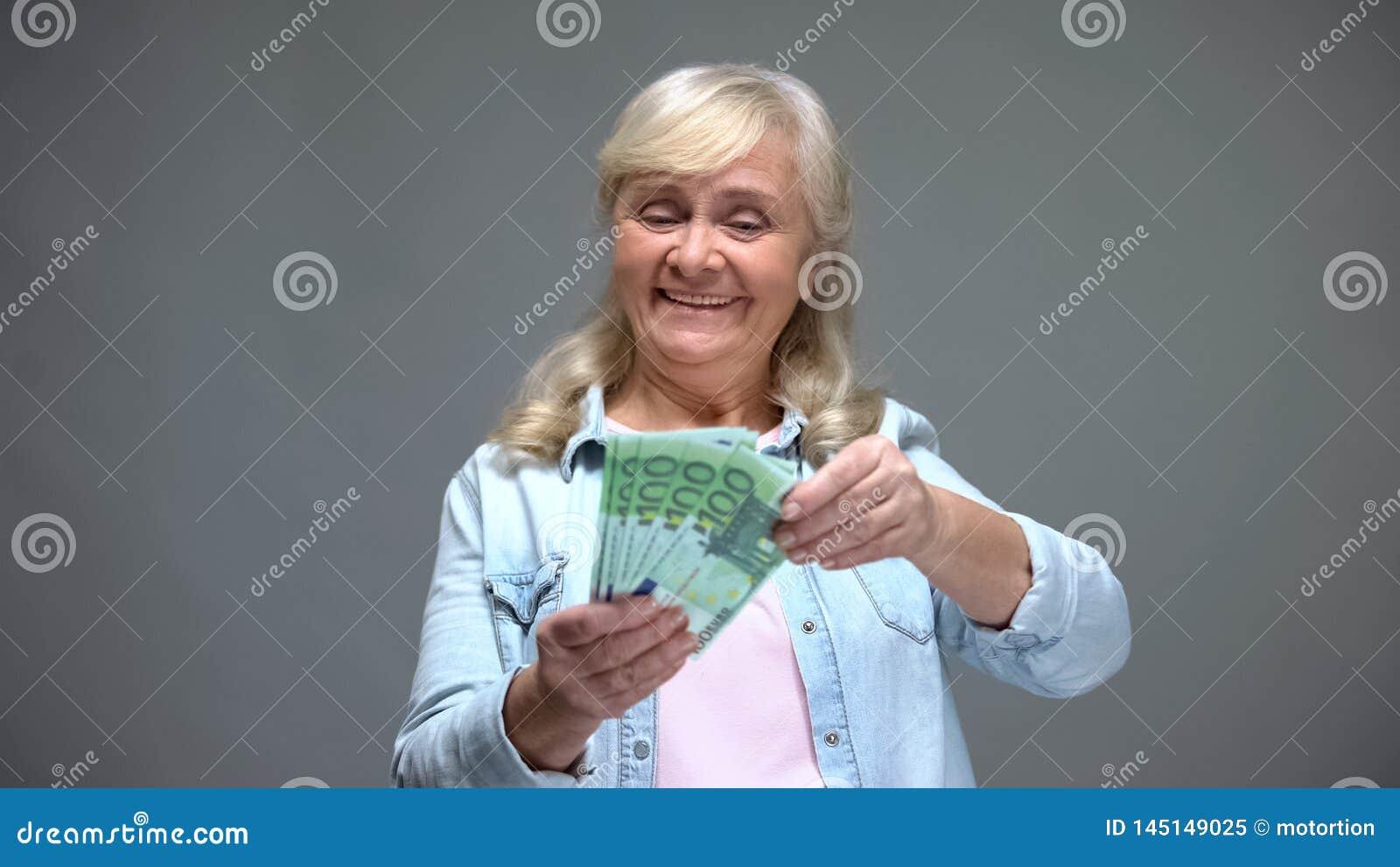 Billetes de banco euro de cuenta femeninos mayores emocionados, compras de planificación, servicio de préstamo