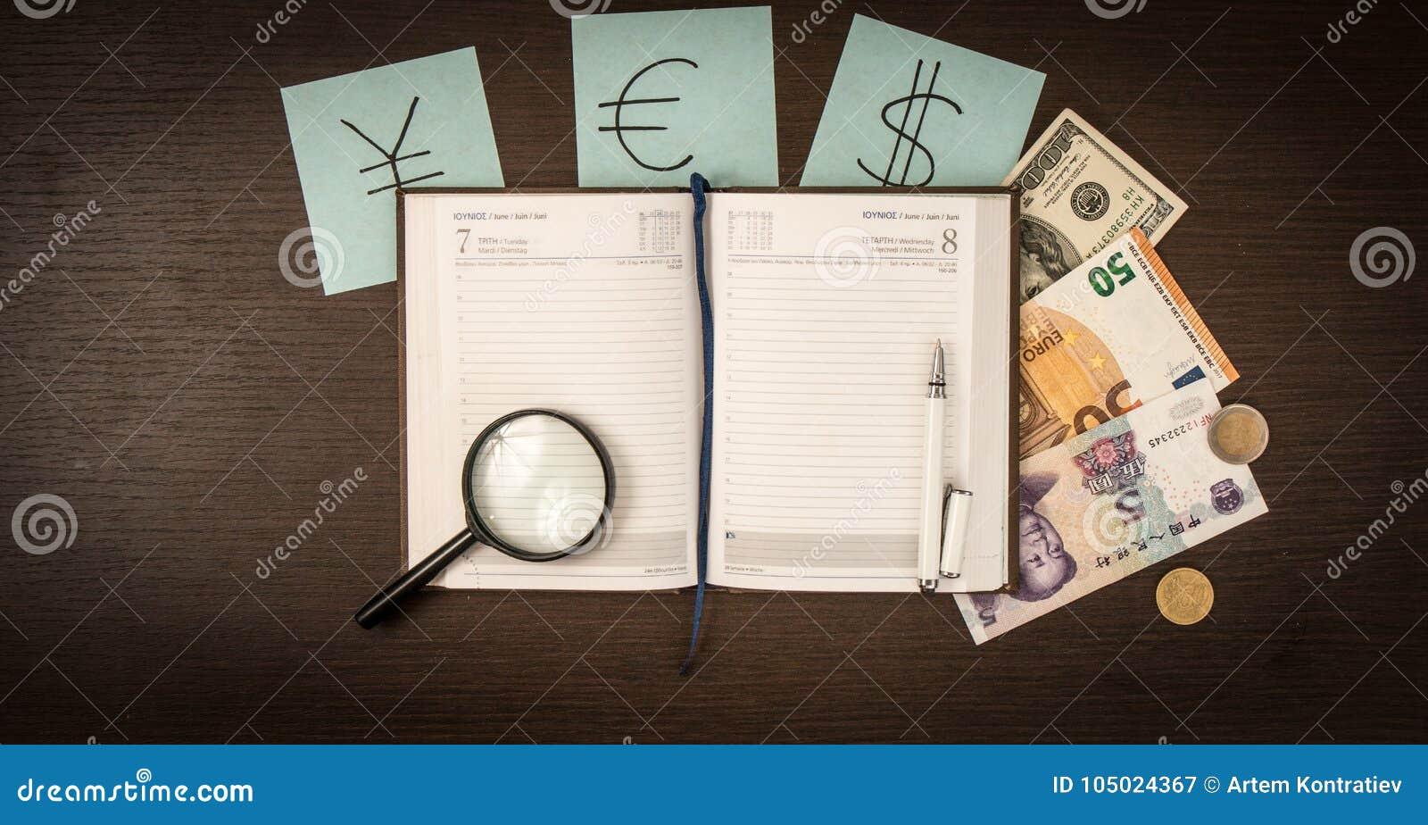 Billetes de banco internacionales, monedas, libreta, etiquetas engomadas con las muestras de moneda en la tabla de madera