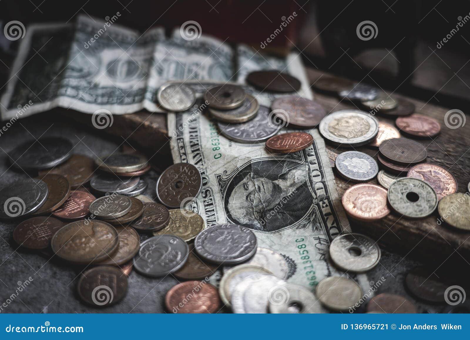 Billetes de dólar y monedas dispersados alrededor en la tierra con la caja concreta y de madera como contexto