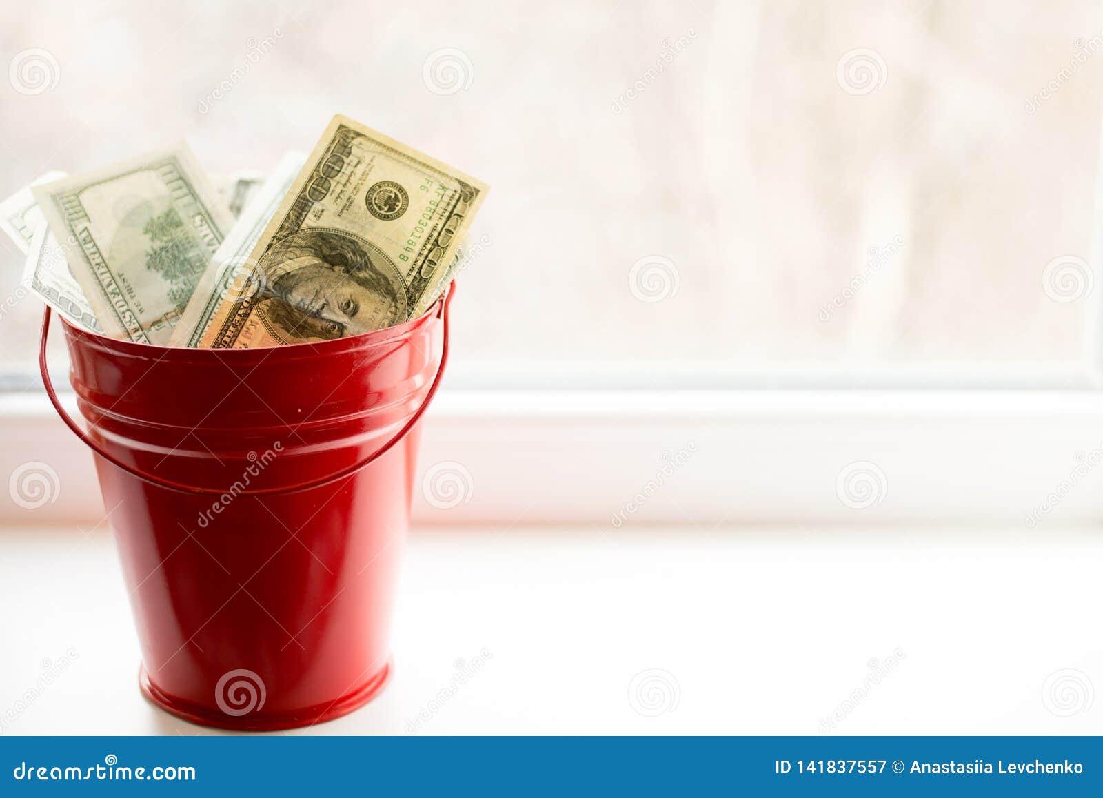 Billets d un dollar dans le seau rouge sur la fenêtre blanche Fond clair Vue supérieure Beaucoup d argent