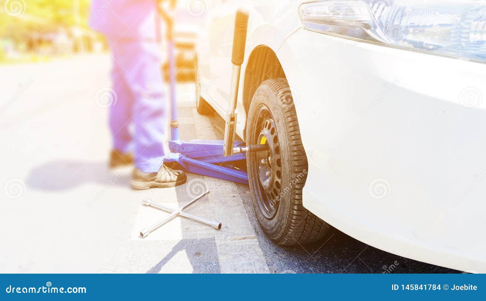 Bilmekanikern som byter ut plana gummihjul p? v?gen Bl?a hydrauliska bilgolvst?lar lyfter bilarna, och hjulskiftnyckeln f?rlade n