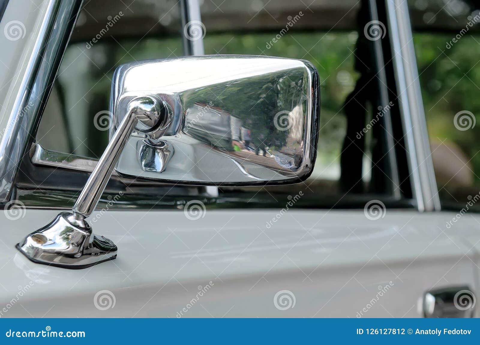 Bilspegel i en kromcasing på en grå bil