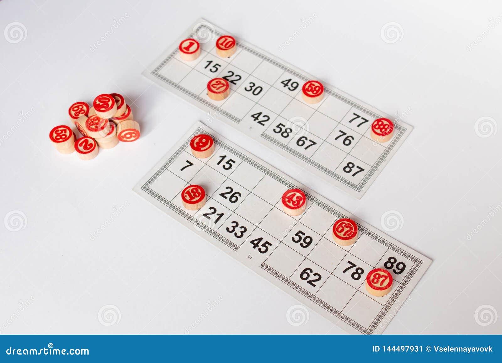Bingo eller lottolek Träkaggar av lottot på kort Kort och chiper för att spela bingo på en vit tabell