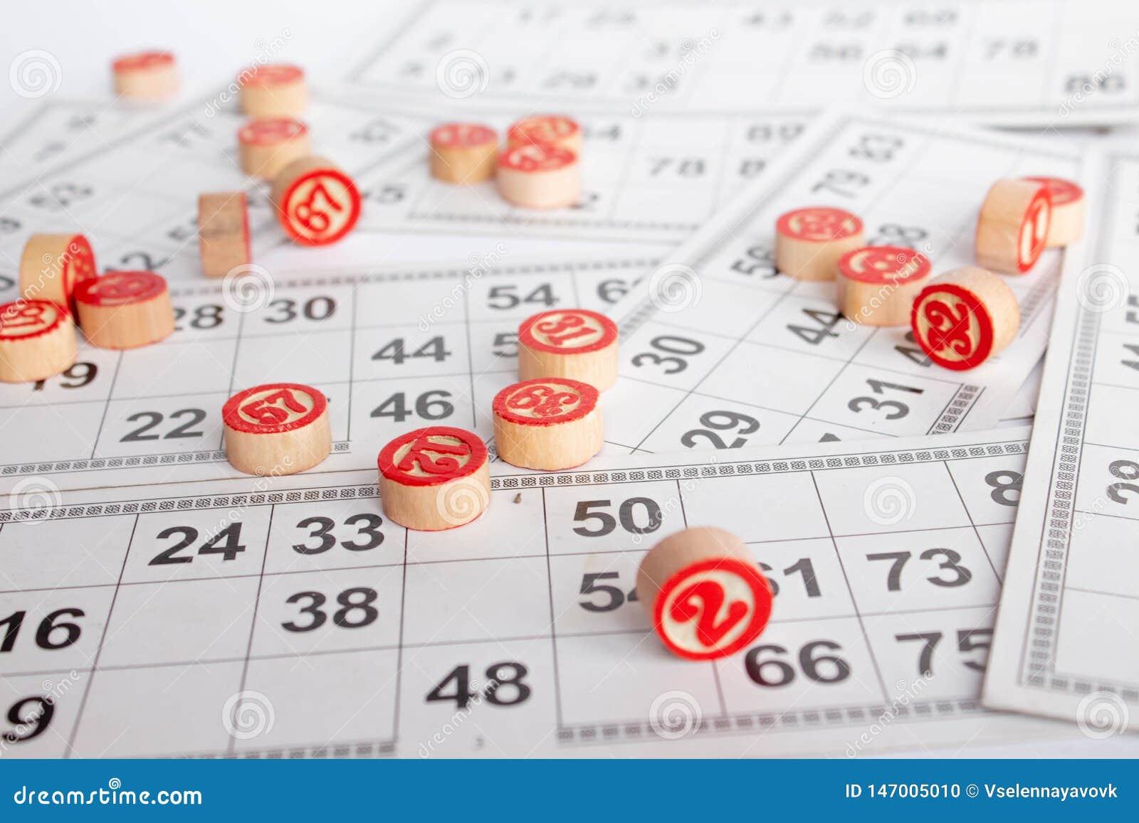 Bingo ou jogo do loto Barris de madeira do loto em cart?es Cart?es e microplaquetas para jogar o bingo em uma tabela branca