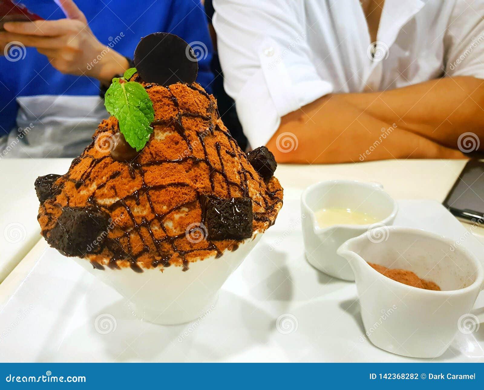 Bingsu dessert on blurred people as a background, Closeup choco volcano bingsu