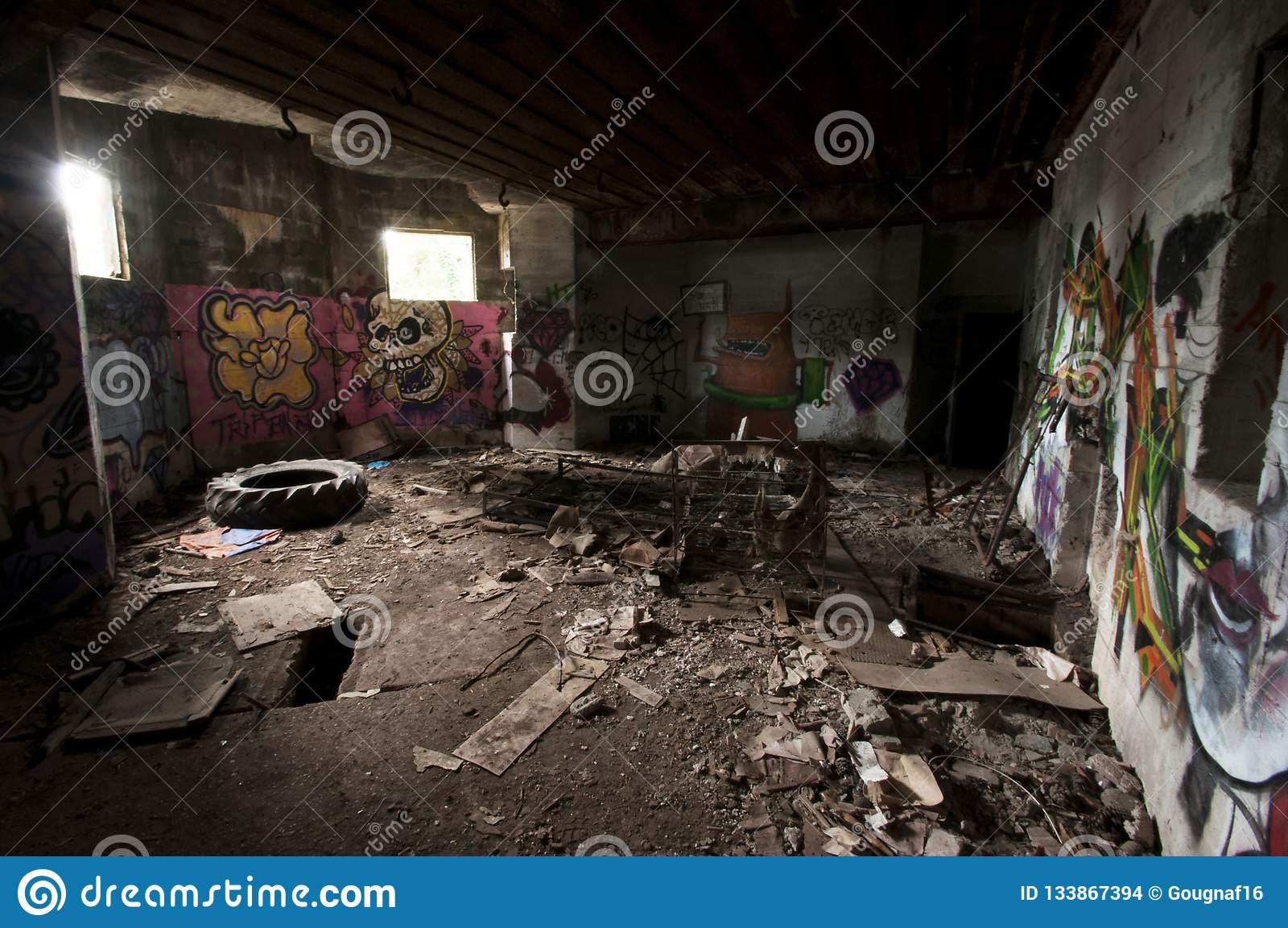 Binnen een verlaten concrete casemate van WO.II met graffiti en het skelet van een metaalbed op de Franse Atlantische kust